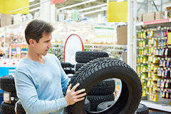 Man chooses winter studded tires for car in supermarket. Man chooses a winter studded tires for a car in a supermarket Royalty Free Stock Photos
