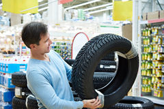 Man chooses winter studded tires for car in supermarket Royalty Free Stock Photo