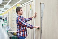 Man chooses wooden door in building store Royalty Free Stock Photos