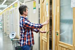 Man chooses wooden door in building store Stock Image