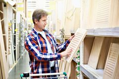 Man chooses wooden facades for furniture in store royalty free stock photo