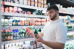 An emotional man chooses yogurt in the milk department of the supermarket. The man buyer buys the products. A man chooses a yogurt in the milk department of the royalty free stock photos