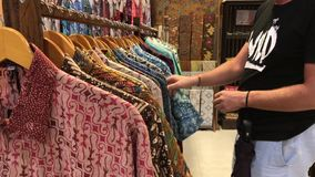 Man choosing a balinese batik shirt in the store. Shopping for men in Asia concept. Cotton shirt. stock video