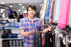 Man choosing belts in shop. Young happy male in the shop choosing leather belts Stock Image