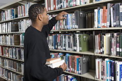 Man Choosing Book From A Shelf Royalty Free Stock Images