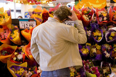 Man choosing bouquet of fresh flowers in grocery store Stock Photography