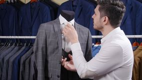 Man choosing business suit at men clothing store. Elegant man choosing business suit at men clothing store stock footage