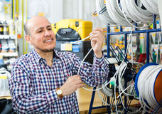 Man choosing cable in household store Royalty Free Stock Photos