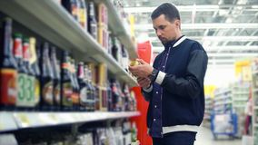 Man choosing a can of beer in the supermarket stock video footage
