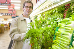 Man choosing carrots in grocery store Royalty Free Stock Photos