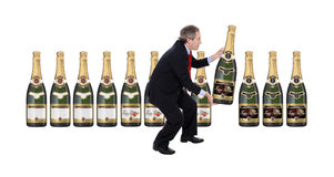 Man choosing a champagne bottle. Man choosing a big champagne bottle isolated on white - New Year Label Stock Photos