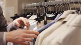 Man choosing clothes in clothing store. Sale, shopping, fashion, style and people concept - man choosing clothes in mall or clothing store stock video