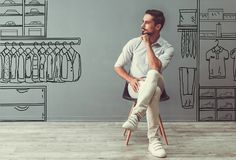 Man choosing clothes. Handsome man in smart casual clothes is looking away and thinking while sitting on the chair on gray background with drawn men`s store Royalty Free Stock Photos