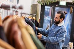 Man choosing clothes at vintage clothing store. Sale, shopping, fashion and people concept - man choosing clothes at vintage clothing store Stock Photography