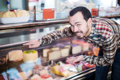 Man choosing delicious cheese. In supermarket Stock Images