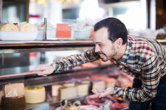Man choosing delicious cheese. Young man choosing delicious cheese in supermarket Royalty Free Stock Photography