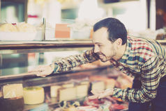 Man choosing delicious cheese. Young man choosing delicious cheese in supermarket Royalty Free Stock Image