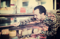 Man choosing delicious cheese. Young man choosing delicious cheese in supermarket Royalty Free Stock Photos