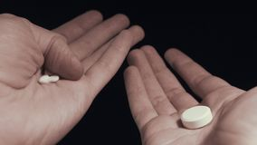 Man choosing between few small pills and one big pill on his hands take them all stock footage