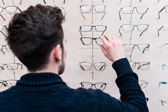 Man choosing glasses from shelf in optician shop Royalty Free Stock Photo