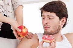 Man choosing junk food. Instead of healthy food Royalty Free Stock Photo