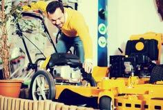 Man choosing lawnmower Royalty Free Stock Images