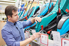 Man choosing lawnmowers in supermarket Royalty Free Stock Photos