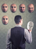 Man choosing a mask. Man looks at the different masks hanging on the wall Royalty Free Stock Photography