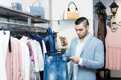 Man choosing new female garment Royalty Free Stock Images