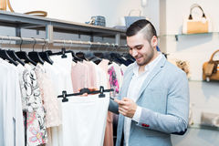 Man choosing new female garment Stock Image