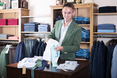 Man choosing new shirt in male cloths store. Young man choosing new shirt in male cloths store Stock Images