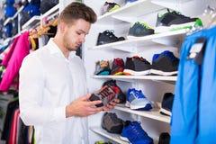 Man choosing new sneakers Stock Image