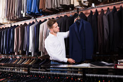 Man choosing new suit. Handsome guy deciding on new suit in men's cloths shop Royalty Free Stock Images