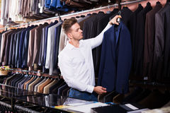 Man choosing new suit. Handsome guy deciding on new suit in men's cloths store Royalty Free Stock Images