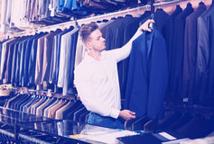 Man choosing new suit. Handsome guy deciding on new suit in men's cloths store Royalty Free Stock Photos
