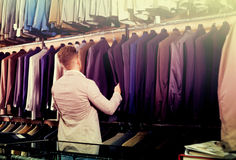 Man choosing new suit. Positive guy deciding on new suit in men's cloths store Stock Photography