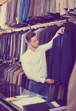 Man choosing new suit. Positive young man deciding on new suit in men's cloths shop Royalty Free Stock Photography