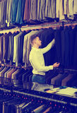 Man choosing new suit. Positive young men deciding on new suit in men's cloths store Royalty Free Stock Photography