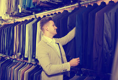 Man choosing new suit. Smiling guy deciding on new suit in men's cloths store Stock Photo