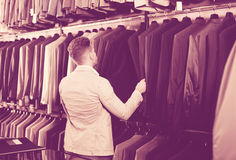 Man choosing new suit. Smiling young man deciding on new suit in men's cloths shop Stock Image