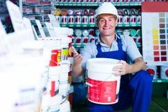 Man choosing paint bucket Stock Photos