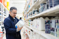 Man choosing paint on the shelves of a hardware store. Man choosing paint on the shelves of a hypermarket shopping center hardware store Royalty Free Stock Images