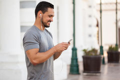 Man choosing a playlist before working out. Profile view of a male runner wearing earbuds and selecting the right playlist on a smartphone for his training Royalty Free Stock Photography