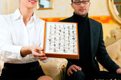 Man choosing a ring at the jeweller. And gets consultancy by a shop assistant Stock Photo