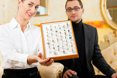 Man choosing a ring at the jeweller. And gets consultancy by a shop assistant Stock Photography
