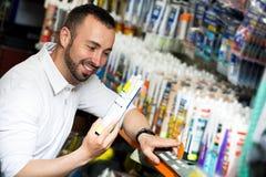 Man choosing sealant tube Stock Image