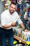 Man choosing sealant tube Stock Photography