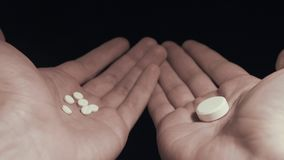 Man choosing between several small pills and one big pill on his hands POV stock video footage