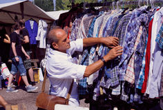 Man choosing shirt on sale of outdoor flea market Royalty Free Stock Images