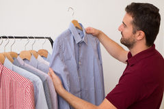 Man choosing shirts in several colors and textures Stock Photo